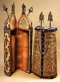 An open torah scroll on rollers in an ornate case and a closed case in a similar style